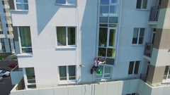 Man hangs on rope and scrubs window of tall living house. Aerial view Stock Footage