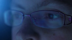Reflection in the eye and glasses of the monitor screen when woman surfing the Stock Footage