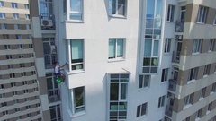 Climber hangs on cable and washes window of tall living house. Stock Footage