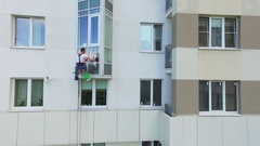 Man hangs on rope and cleans window of tall residential house Stock Footage