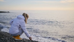Beautiful blonde woman trying temperature of water by hand. Coming waves forces Stock Footage