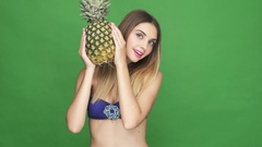 Smiling girl in bikini peeping out of pineapple and looking at camera Stock Footage