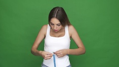 Upset young woman measuring her waist and getting disappointed Stock Footage