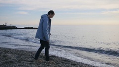 Young man throwing stones into the ocean Stock Footage