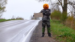Man with pumpkin on head stand with written sign on roadside, ask why so serious Stock Footage