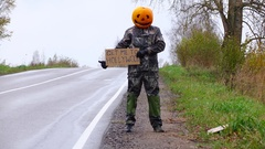 Pumpkinhead man try to hitch a ride with carton sign, Get Me To Hollywood Stock Footage