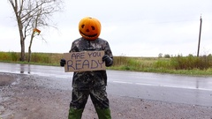 Jack Pumpkinhead stand under rain with written sign, ask Are You Ready Stock Footage
