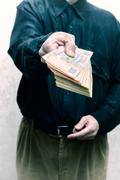 Businessman, or politician, offering a Hryvnia banknotes bribe for corrupti.. Stock Photos