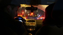 Couple in car, vehicle stand in congestion at red light, night traffic jam Stock Footage