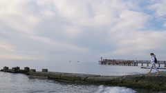 Woman in jacket walk on sea pier. Shot of pier with beautiful sea scenery with Stock Footage
