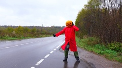 Halloween prank, man thumbing on road with carved pumpkin on head Stock Footage