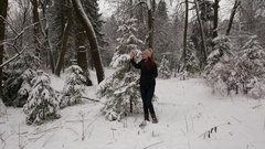 Girl make selfie against small fir tree covered with snow, dusk forest Stock Footage