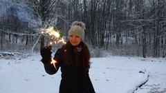 Happy girl hold in hand brightly shining sparkler, snowy park opening, slowmo Stock Footage