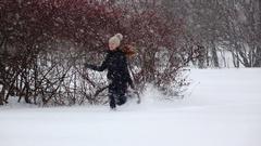 Happy girl run through snowfall, deep fluffy snowbank, slow motion Stock Footage