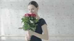 Gorgeous Young Ballet Dancer Holding and  Sniffing Bouquet of Red Roses.  Stock Footage