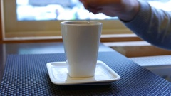 Man take tea spoon and stir his tea, modern tall white cup on square saucer Stock Footage