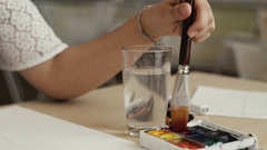 Female artist holding a paint brush, dipping in to color and water Stock Footage