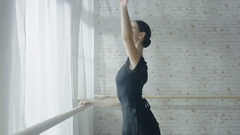 Mid Shot of a Young and Beautiful Ballerina Dancing at the Barre.  Stock Footage
