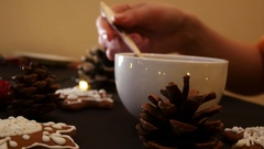 Woman stirs hot tea on a background of cakes, cones and garland lights Stock Footage