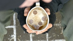 Falling cents in to the cup of homeless man. Slow motion. Stock Footage