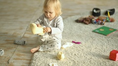 Little blonde girl trying to put socks on Stock Footage
