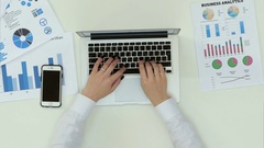 Woman's hands typing on laptop at office desk with statistics graph Stock Footage