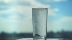 Aspirin splash in glass in slwo motion, headache solution on blurred city Stock Footage