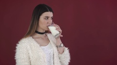 Girl drinking a glass of milk on the red background Stock Footage