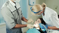 Dentist with tools inspects the jaw of the patient sitting in a chair Stock Footage