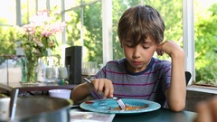 Young boy eating lunch supper 8 year old kid eating Stock Footage