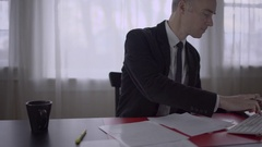 Man with jacket doing paperwork at his desk Stock Footage