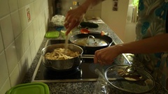 Young woman at the kitchen cooking supper for kids Stock Footage
