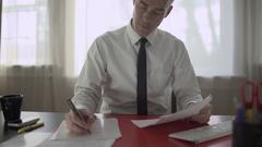 Entrepreneur doing paperwork at his desk Stock Footage