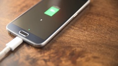 4K Motion view of charging smartphone on wooden table Stock Footage