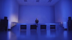A young man sits alone on an empty dance floors and uses laptop to invite Stock Footage