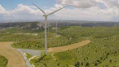 Wind turbine blades rotating on amazing green hills, alternative energy source Stock Footage