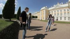 Woman photographer photographing a man in a park the Upper Garden, Peterhof Stock Footage