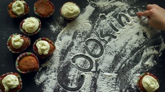 Cooking concept. Top view of inscription word cooking on white flour. Stock Footage