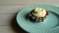 Muffin cake with butter cream on plate at wooden table. One cupcake with cream Stock Footage