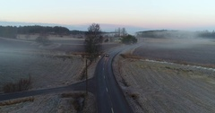 Cinema 4k aerial tilt view just above a car on a slippy road, at foggy fiel.. Stock Footage