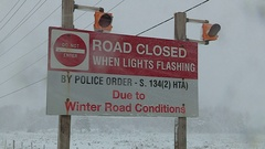 Road closed sign with flashing red lights in snow storm Stock Footage