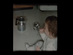 Baby boy plays with antique coffee percolator Stock Footage