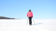 Winter tourist with snowshoes walk in snowy drift. Hiker in pink sports jacket Stock Footage