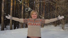 Attractive middle-aged woman throws up soft snow. Stock Footage