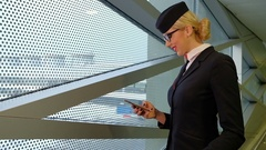 Stewardess is reading a message on your smartphone and smiles Stock Footage
