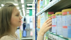 Young mother choose baby food in store Stock Footage