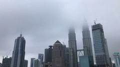 Kuala Lumpur city skyline during hazy, misty and cloudy morning. Tilt down Stock Footage