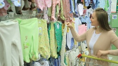 Mother choose clothes for baby in store and put it cart Stock Footage