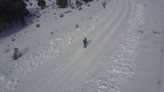Aerial man walks along mountain road winter snow following 4K Stock Footage