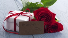 Three red roses with gift box on blue table and falling petals in slowmo Stock Footage